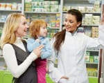 Cheerful pharmacist chemist woman demonstrating vitamins to chil