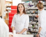 Happy pharmacist helping customer in drug store