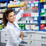Beautiful smiling young woman pharmacist doing his work in pharm